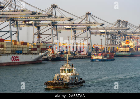Laem Chabang seaport, Thailand - March 17, 2019: Rows of gray container cranes, colorful stacks of boxes, and a line of container ships with one tugbo - Stock Photo