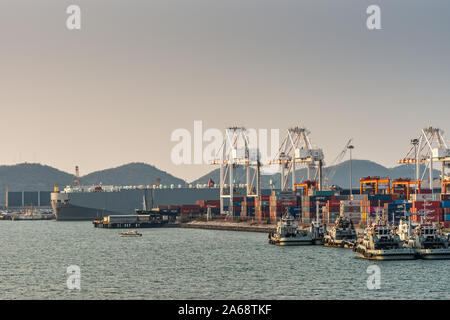 Laem Chabang seaport, Thailand - March 17, 2019: Tall large gray vehicles transport ship behind container terminal with its cranes and stacks of color - Stock Photo