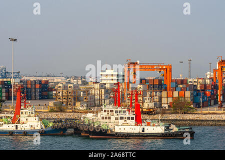 Laem Chabang seaport, Thailand - March 17, 2019: Rows of anchored tugboats in front of container yard with stacks and orange transporters like bridges - Stock Photo
