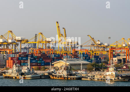 Laem Chabang seaport, Thailand - March 17, 2019: Chaotic scene of container terminal with yellow cranes, stacks of colored boxes and a few tugboats in - Stock Photo
