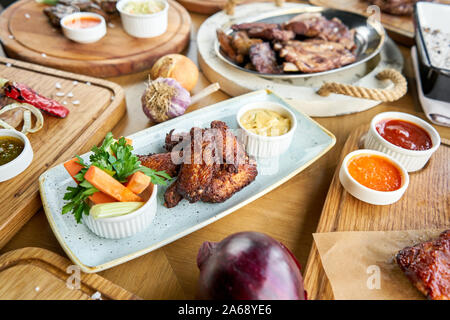 Chicken wings fries. Barbecue restaurant menu. Many different food on the table. Dinner party or Banquet. - Stock Photo