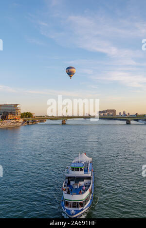 View of Rhine River, promenade on riverside, Deutzer Brücke, flying balloon, Deutzer Hafen, tourist cruise and background of sunset and twilight sky. - Stock Photo