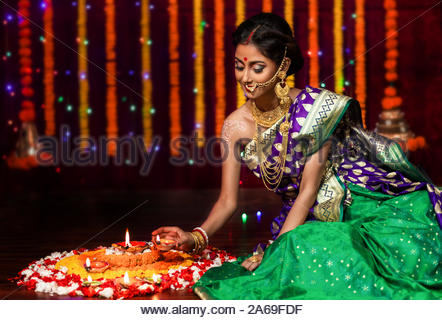 Beautiful young Indian woman in traditional sari dress holding a oil lamp light or diya and decorating floor with flowers on the occasion of Diwali - Stock Photo