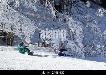 PYRENEES, ANDORRA - FEBRUARY 12, 2019: Two snowboarders sit photographed on the slope among branches in the snow. Pyrenees, Andorra, winter sunny day - Stock Photo