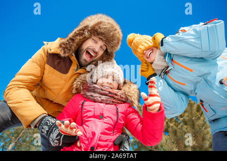 Winter vacation. Family time together outdoors grimacing to camera laughing playful bottom view close-up - Stock Photo