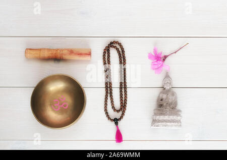 Meditation or mindfulness concept. Wooden mala beads, tibetan singing Bowl with symbol OM  and Buddha statue with flower on wooden background with cop - Stock Photo