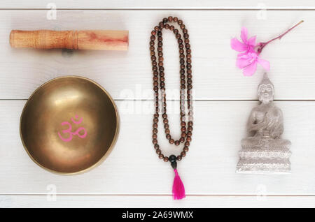 Essential accessory for mindfulness or meditation. Wooden mala beads, tibetan singing Bowl with symbol OM   and Buddha statue with flower on wooden ba - Stock Photo