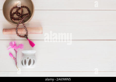 Meditation or mindfulness concept. Wooden mala beads, tibetan singing bowl and  white oil burner with flower on wooden background with copy space. - Stock Photo