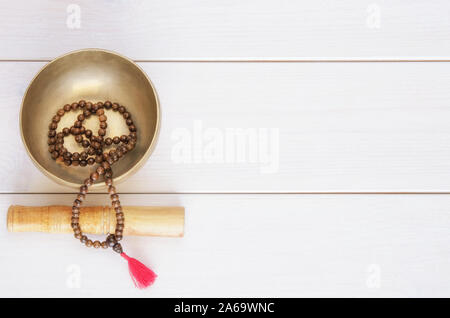 Traditional mala beads and tibetan singing bowl on white wooden background with copy space. Essential accessory for mindfulness or meditation. - Stock Photo