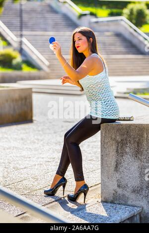 Time out for fixing makeup using small handy mirror legs and heels heelsaddicted - Stock Photo