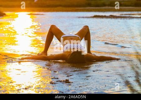 Overstretched on beach in sunset time late day spreading arms and legs in shallow water sea - Stock Photo