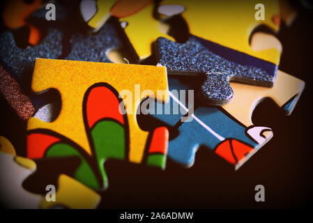 Puzzle pieces scattered on a dark background close up. Retro style toned - Stock Photo