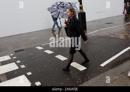 After heavy rainfall, Londoners and visitors walk along Long Acre, Covent Garden, on 24th October 2019, in Westminster, London, England. - Stock Photo