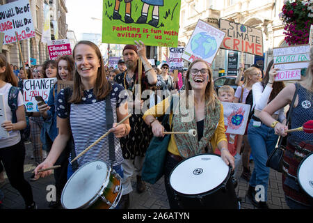People of all ages gather for the Global Climate Strike organised by UK Student Climate Network on 20th September 2019 in Birmingham, United Kingdom. The School strike for climate, also known as Fridays for Future, Youth for Climate and Youth Strike 4 Climate, is an international movement of school students who are deciding not to attend classes and instead take part in demonstrations to demand action to prevent further global warming and climate change. UK Student Climate Network is calling on everyone - adults, workers, community groups, trade unionists, nurses, teachers, steel workers, car - Stock Photo