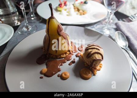 Delicious dessert from a gastronomic restaurant in Paris (France). Pear, caramel ice cream with exquisite chocolate coulis. French food - Stock Photo