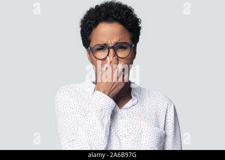 Head shot unhappy African American woman in glasses closing nose - Stock Photo