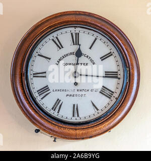 Old clock showing the time as sixteen minutes past twelve. - Stock Photo