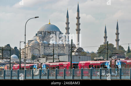 ISTANBUL TURKEY RED TRAM AND FISHERMEN ON THE GALATA BRIDGE WITH THE SULEYMANIYE MOSQUE IN THE BACKGROUND - Stock Photo