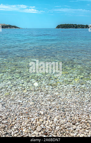 Gravel beach and shallow sea - Stock Photo