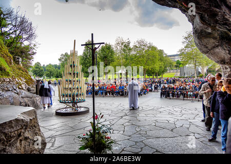 LOURDES - JUNE 15, 2019: view of the cave, the cathedral and the faithful of the Sanctuary of Lourdes, France - Stock Photo