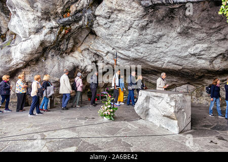 LOURDES - JUNE 15, 2019: View of faithful walking along the holy cave, Lourdes, France - Stock Photo