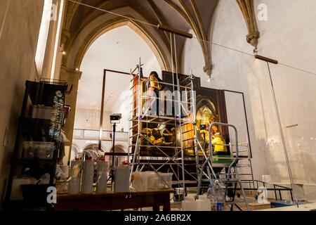 Colmar, France. 25th Oct, 2019. Two restorers are working on a panel of the Isenheim altar in the Museé Unterlinden. The altar is currently undergoing extensive restoration. Credit: dpa picture alliance/Alamy Live News - Stock Photo