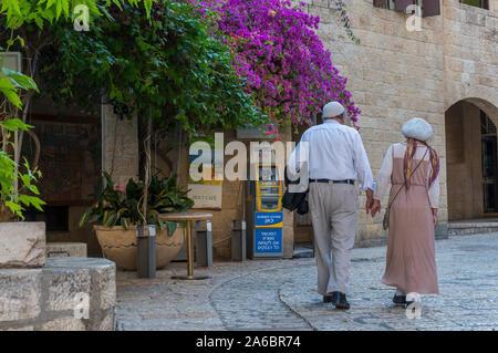 Living in Jerusalem. Everyday life in sacred city of Jerusalem.  Old couple walking hand on hand in Armenian Quarter of Jerusalem - Stock Photo