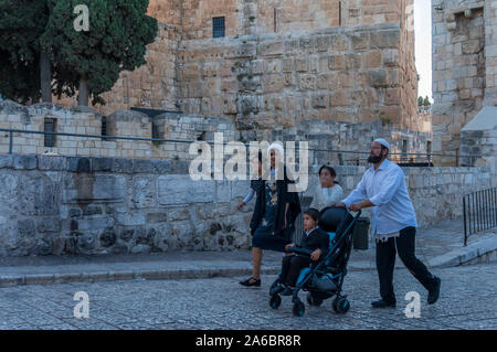 Living in Jerusalem. Everyday life in sacred city of Jerusalem.  Mother with two little girls relaxing in a sabbath day in old city of Jerusalem. - Stock Photo