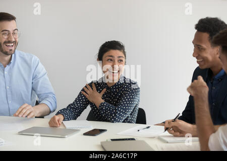 Positive young coworkers discussing project and laughing - Stock Photo