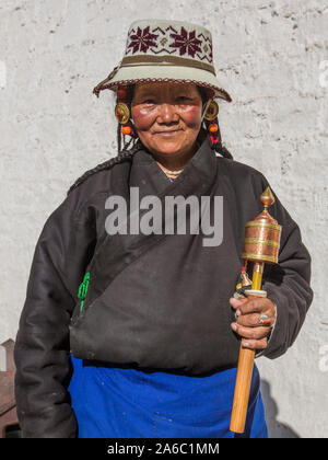 A Khamba Tibetan woman from the Kham region of eastern Tibet on a pilgrimage to visit holy sites in Lhasa, Tibet.  She is wearing red coral jewelry. - Stock Photo
