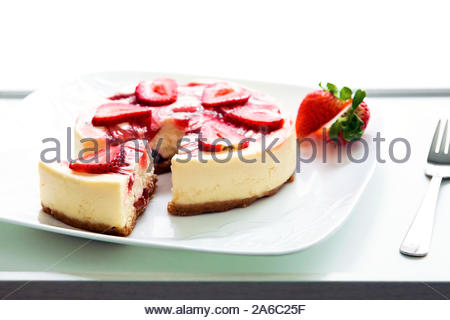 A beautiful, traditional strawberry cheesecake presented on a white plate in front of a bright light with sliced strawberrys and partially sliced. - Stock Photo