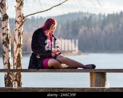 Leisurly seated on wooden bench looking away into distance background - Stock Photo