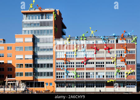 View of modern architecture with funny climbing figures at Media Harbour. Medienhafen business and offices district in Dusseldorf city, Germany - Stock Photo
