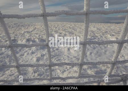 Wire fence covered in hoar frost on Whernside carpeted in snow and ice mid winter Yorkshire Dales