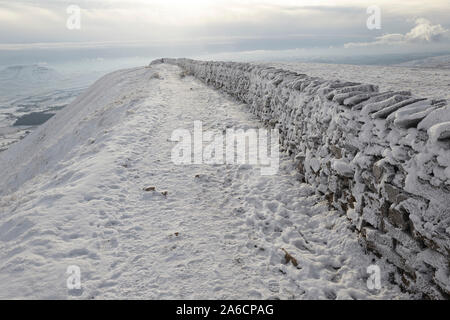 Dry stone wall covered in hoar frost on Whernside carpeted in snow and ice mid winter Yorkshire Dales