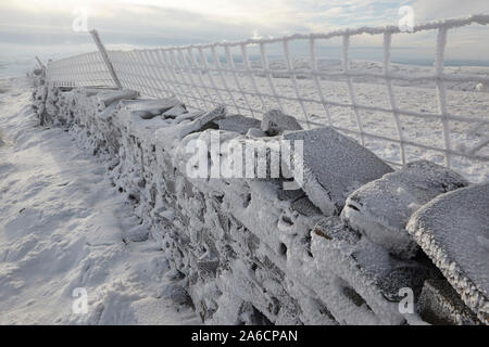 Dry stone wall and wire fence covered in hoar frost on Whernside carpeted in snow and ice mid winter Yorkshire Dales