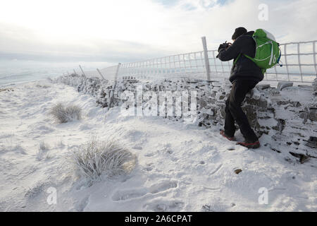 Walker taking photographs of hoar frost on a dry stone wall, Whernside carpeted in snow and ice mid winter Yorkshire Dales