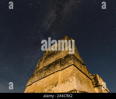 The the stars of the Milky Way over the tall roof comb of Temple II in the ruins of the Mayan city of Tikal in Tikal National Park in Guatemala. - Stock Photo