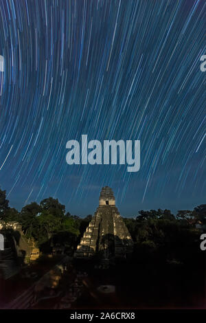 Temple I, Temple of the Jaguar, by the light of the full moon at night with star trails, Tikal National Park, Guatemala. - Stock Photo
