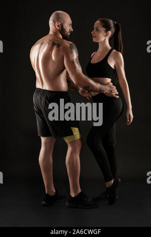 Athletic man in shorts and sneakers with brunette woman in leggings and top posing on black background. Fitness couple, gym concept. - Stock Photo