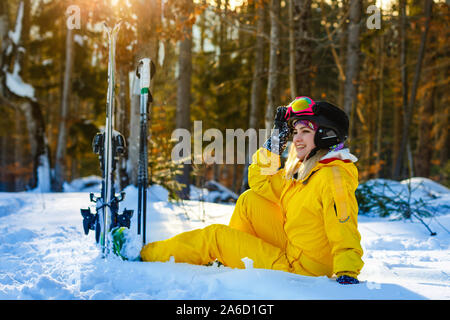 Thoughtful girl with mountain skiing sitting on a ski slope and looks into the distance - Stock Photo