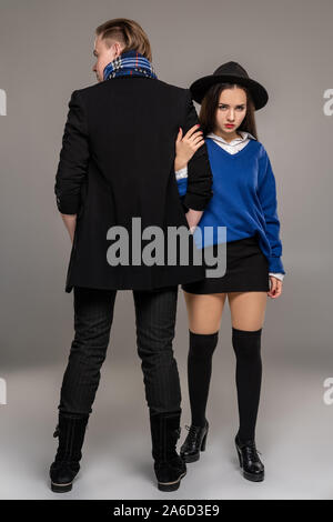 Studio shot of a beautiful young woman and man posing over a gray studio background. - Stock Photo