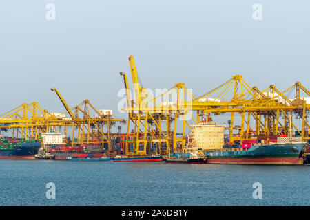 Laem Chabang seaport, Thailand - March 17, 2019: Several docked container ships of different sizes being worked by yellow cranes under sunset sky. - Stock Photo