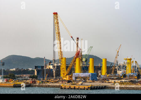 Laem Chabang seaport, Thailand - March 17, 2019: Tall cranes cranes and metal cylinders together with a chaotic scene of the construction site for a l - Stock Photo