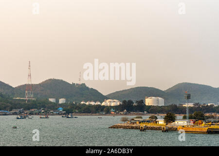 Laem Chabang seaport, Thailand - March 17, 2019: White spheres and classic tanks for LNG gas and petrol products behind screen of trees and forested h - Stock Photo