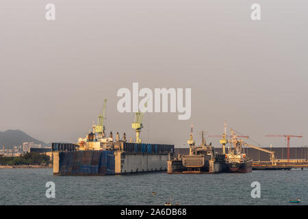 Laem Chabang seaport, Thailand - March 17, 2019: Two dry docks, one large and one small, with ship inside under sunset sky. - Stock Photo
