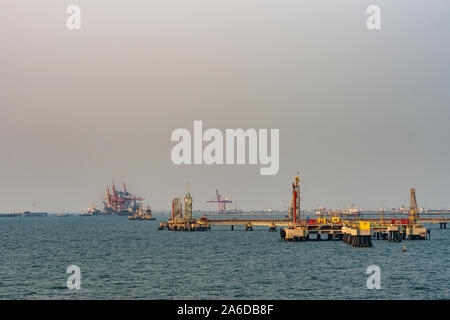 Laem Chabang seaport, Thailand - March 17, 2019: Off coastline,  red-yellow hookup and anchoring platform for oil tankers to unload their product. Ple - Stock Photo