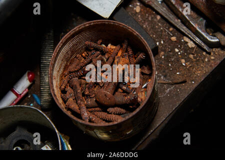 Rusty bolts and screws in metal box on the workbench. - Stock Photo