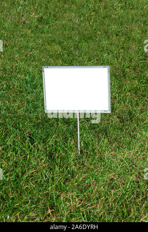 A sign with an inscription on the grass - Stock Photo