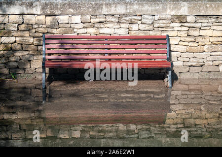 park bench with its feet in water and reflection against a stone wall ,effects of global warming & water levels rising.  Vaucluse.France